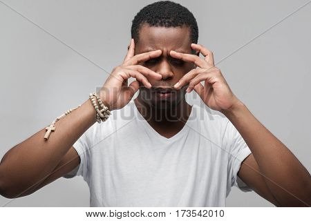 African man with concentrated in deep thoughts. Trying to remember important thing. Memory, brainstorm, inspiration. Portrait on grey background.