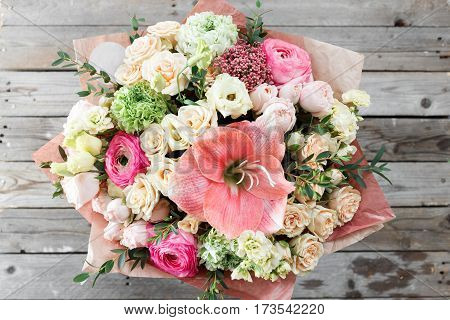 mix flowers bouquet on wooden background. old rustic table a coil of twine and garden secateurs. top view.