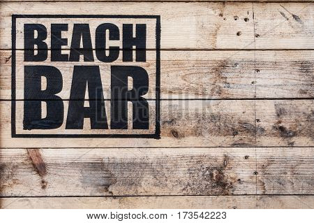 close up view of beach bar logo stamped on wooden surface