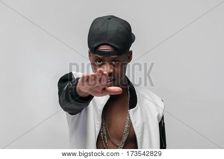 Black afroamerican guy gang member portrait on grey background with free space. Disgust, loathing, nazis, fascist, neglecting, ghetto, challenge to society, cheeky, cool, rebellious