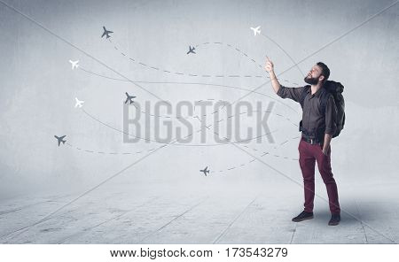 Handsome young man standing with a backpack on his back and little planes in the background
