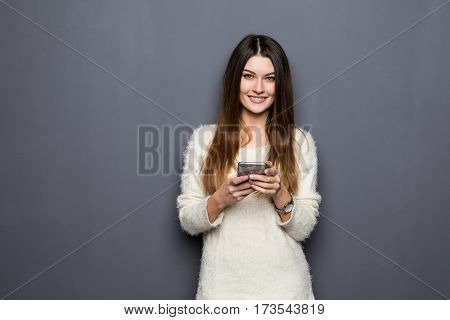 young woman with phone on grey background