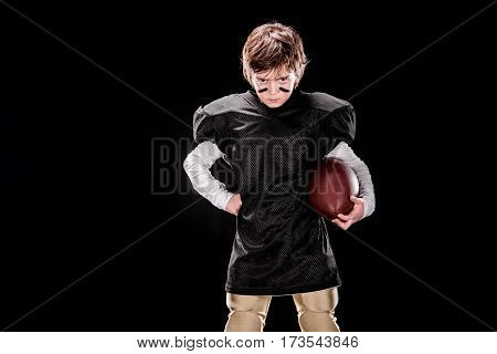 Angry boy american football player holding ball and looking at camera