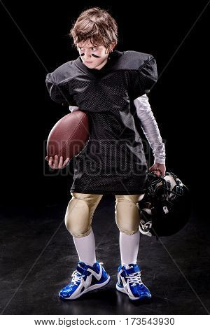 Full length view of angry boy american football player holding rugby ball and helmet