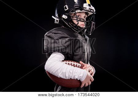 Side view of little boy american football player in uniform holding ball on black