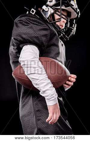 Low angle view of boy american football player holding rugby ball on black