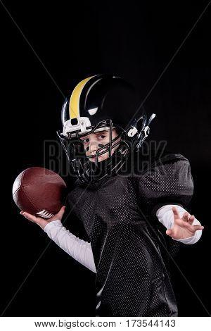 Little boy in sportive uniform and helmet playing american football on black