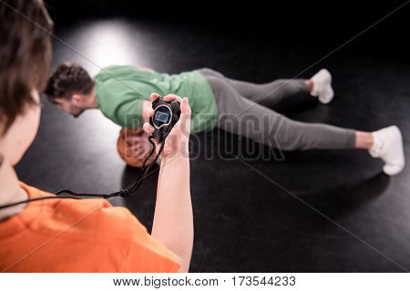 back view of boy with stopwatch controlling time while man doing push ups with ball on black