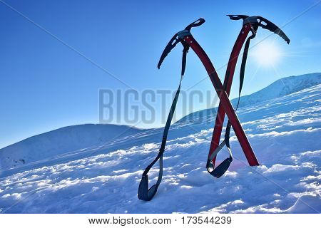 Pair of ice axes on mountain slope