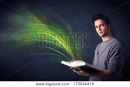 Casual young man holding book with green wave flying out of it