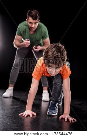 man controlling time while boy training and looking to camera on black