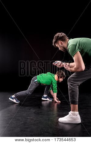 side view of man controlling time while boy training on black