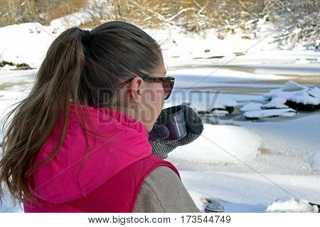 Young woman drinking hot tea on winter forest and watching frozen river.