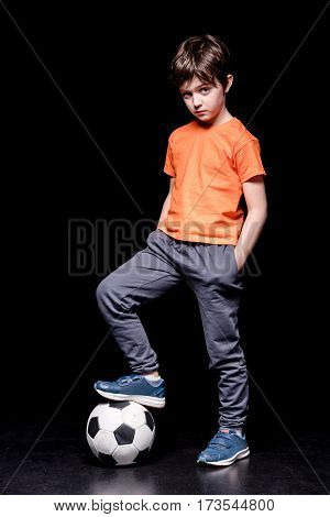 serious boy standing on football ball with one leg and looking to camera on black