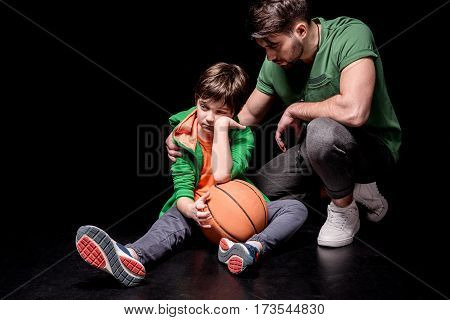 man cheering up upset boy sitting on floor with basketball ball on black