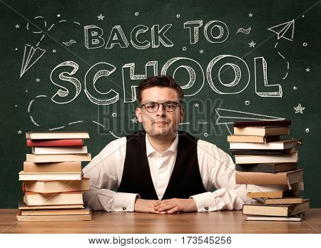 A young teacher in glasses sitting at classroom desk with pile of books in front of blackboard saying back to school drawing concept.