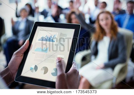 Business interface with graphs and data against businessperson using digital tablet during meeting