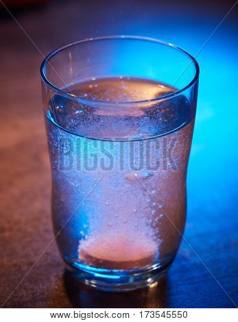 Effervescent tablet in the glass of water containing vitamines and painkillers.