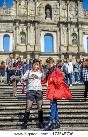 Macau, China - December 8, 2016: tourists take a selfie on staircase of Ruins of St. Paul's in a sunny day.The iconic stone facade, on background, one of the most popular historic attractions in Macau