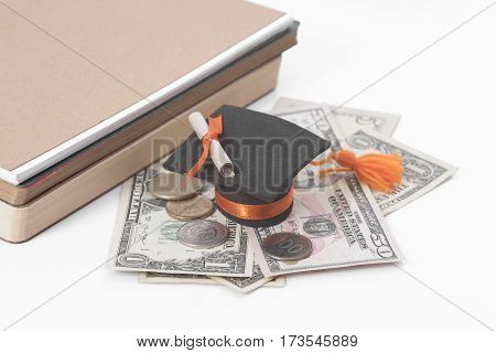 black graduation hat with money book on white table. business finance concept.