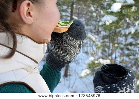 Teenager eating sandwich and holding coffee mug in wintry forest.