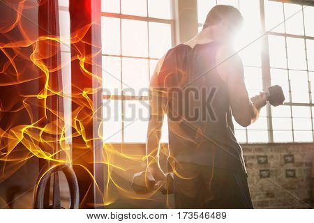 Abstract orange glowing black background against rear view of muscular man lifting dumbbell
