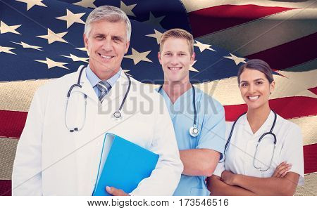 Portrait of doctor holding file with colleagues against waving flag of america