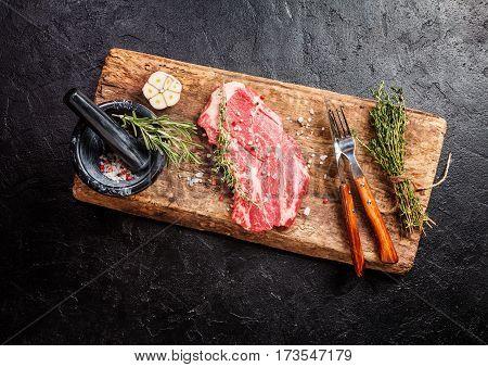 Raw fresh ribeye steak on cutting board on black stone background. Top view