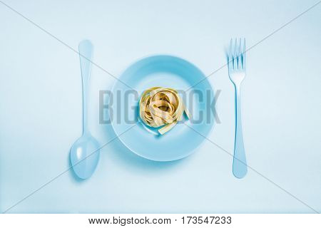 Tagliatelle on a blue plate with blue silverware on a blue background
