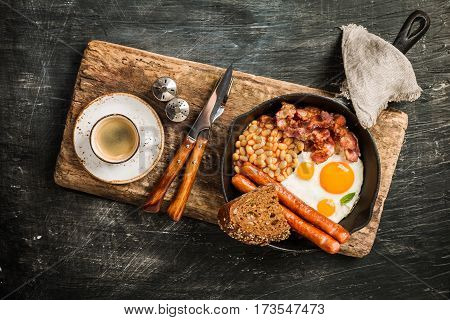 English breakfast - fried egg, beans, tomatoes, sausages, bacon and bread in frying pan on aged board over black background. Top view