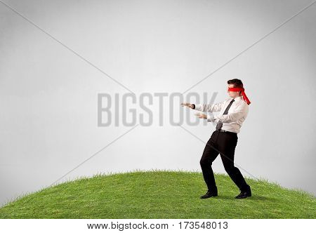 Young blindfolded businessman steps on a patch of grass