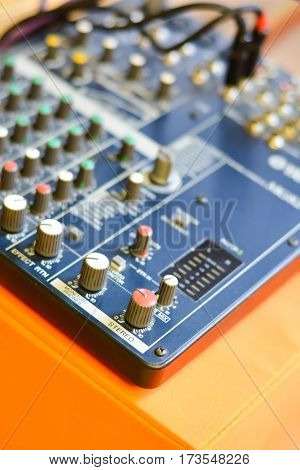 Button control sound mixer on an orange desk