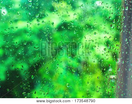 Abstract background with rain drops on window glass and green unfocused background