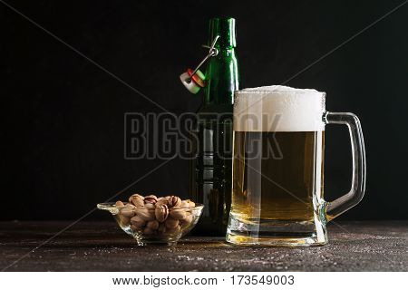 Glass mug of light beer with pistachios on dark background