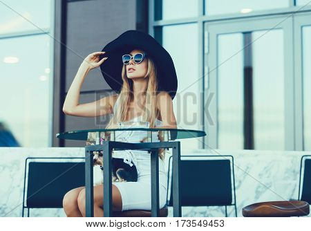 successful fashionable woman in a hat sitting on the terrace of a cafe waiting for a meeting.