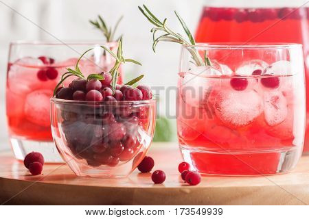 Refreshing drink with cranberries, ice and rosemary on white wooden background, selective focus, copy space