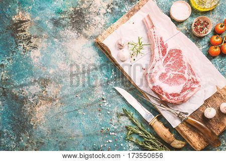 Raw tomahawk beef steak with ingredients for grilling: seasoning, fresh rosemary and olive oil on paper, top view