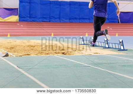 Sportswoman jumping into sandpit on triple jump competition in track and field championship