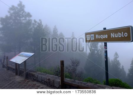 Landmark indicating direction to famous rock Roque Nublo in a foggy day on the Canary Island Gran Canaria Spain - 11.02.2017.