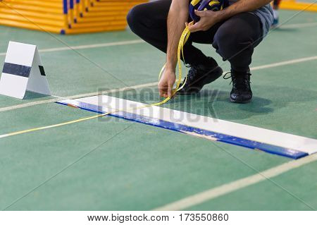 An official taking measure of long or triple jump on track and field competition