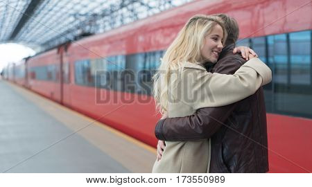 Young embracing couple at the station