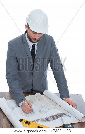 Engineering duties. Vertical shot of a mature male businessman architect in a hardhat working on building plans on blueprints isolated on white business new occupation architectural project planning