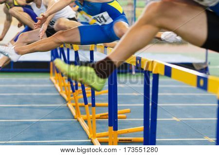 sportsmen running hurdles sprint race in indoor track and field competition