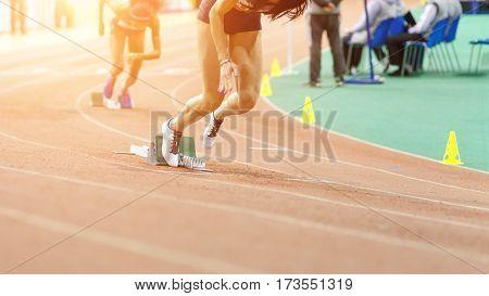 Sportswomen starting running sprint from starting blocks