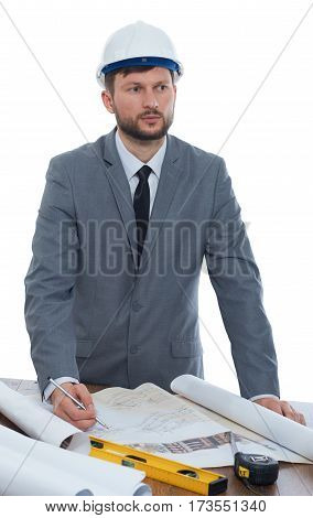 Stuck on ideas. Vertical studio shot of a mature male businessman architect wearing hardhat looking away thoughtfully while working on a building plan concentration think construction engineering