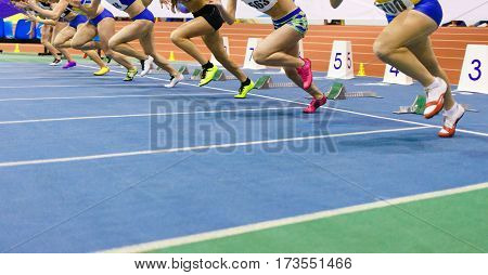 Sportswomen starting run sprint race on track and field competitions