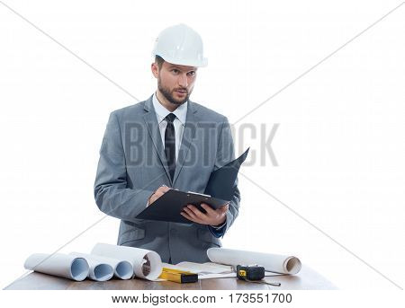 Engineering notes. Mature businessman engineer looking away thoughtfully while writing on his clipboard profession development building architectural project planning engineer profession concept