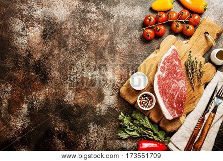 Fresh raw Prime Black Angus beef strip steaks on cutting board over dark rustic concrete background, top view. Ingredients set for making healthy dinner.