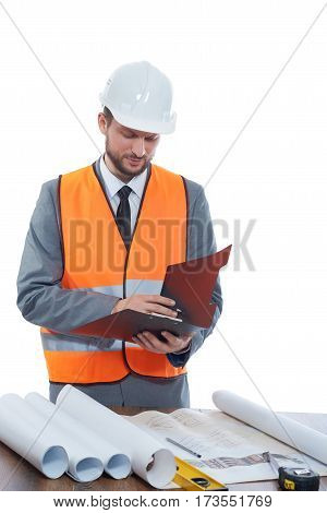 Constructionist businessman. Mature male constructionist wearing safetu vest and a hardhat making notes on his clipboard isolated on white professionalism development confidence experience concept