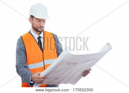 Serious about his job. Professional male construction worker wearing protective helmet and safety vest examining building blueprints isolated on white copyspace experience confidence business builder